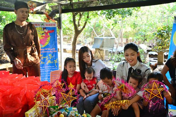 Hai người đẹp phát quà và tổ chức phá cỗ cho các em nhỏ.