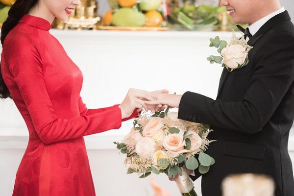 Cặp đôi trao nhẫn cho nhau trong sự chứng kiến của 2 gia đình